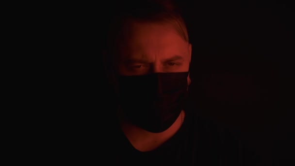 Caucasian man in black medical mask,flashing red and blue neon light on face