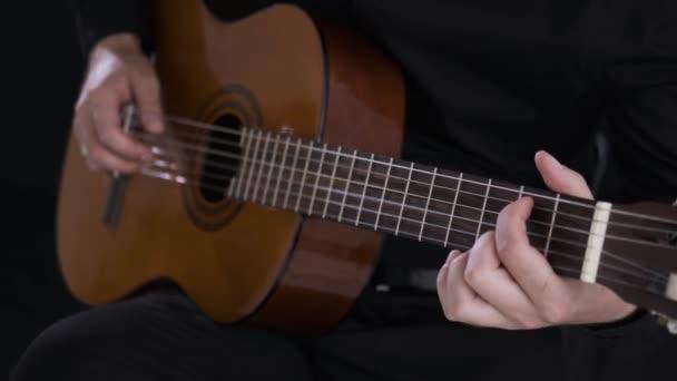muž hraje na akustickou kytaru v hudebním studiu, zblízka, mladý umělec,