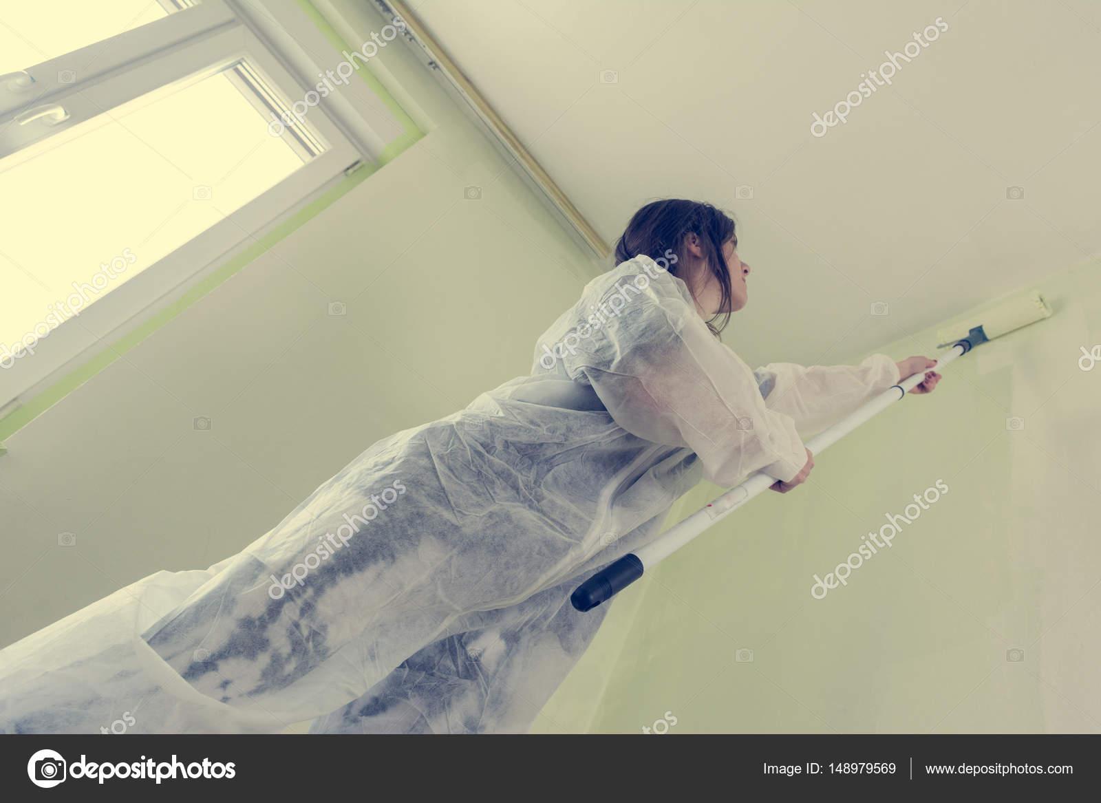 Jonge vrouwelijke student schilderij van haar kamer u stockfoto