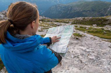 Female trekker studying a map.