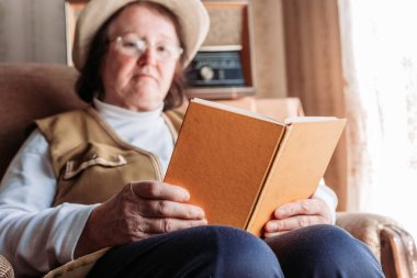 Elderly woman with a hat on, reading a book by the window. Afternoon light