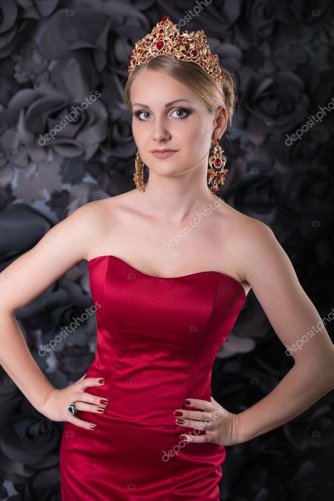 Hermosa joven rubia en vestido largo rojo con falda mullida sobre un ...