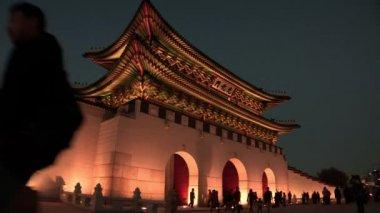 Tourists walking near entrance of Gyeongbokgung Palace
