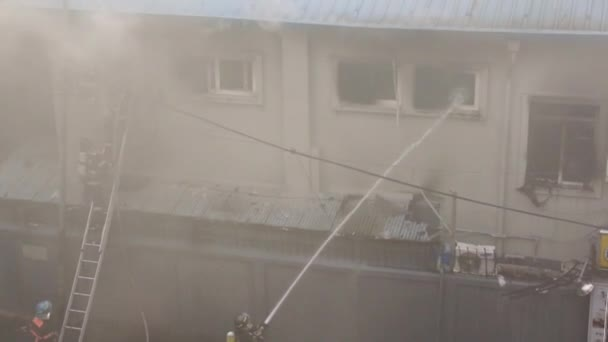 Mužské hasiči hasí oheň venku