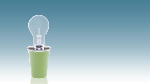 light bulb turning on in flowerpot with grass, energy concept