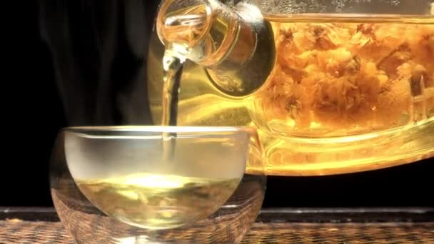Closeup of teapot pouring tea into glass cup