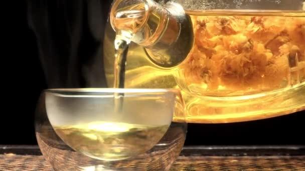 Closeup konvice nalévá čaj do skla pohár