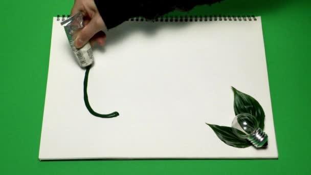 Eco koncept prostředí ženských rukou kreslení eco nápis zelenou barvou na bílém notebook s zelenými listy a žárovka