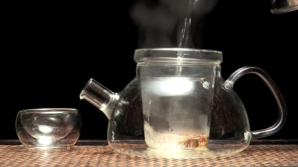 Closeup of glass tea cup, glass teapot with tea and boiling water