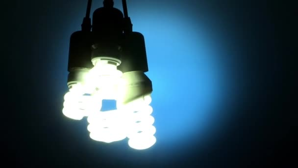 hanged light bulbs flashing and turning off in dark room, energy concept