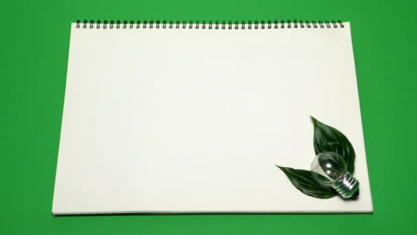 Eco environment concept of white notebook with green leaves, bulb and green paint creating eco lettering