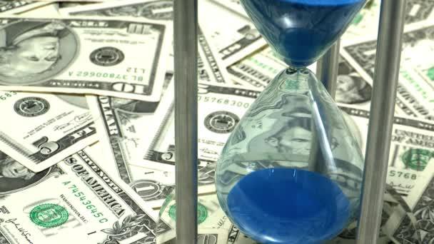 modrý písek v přesýpacích hodin na měnu pozadí