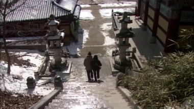 Rear view of people walking downstairs in traditional korean temple