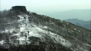 tourists walking up on snowy mountain