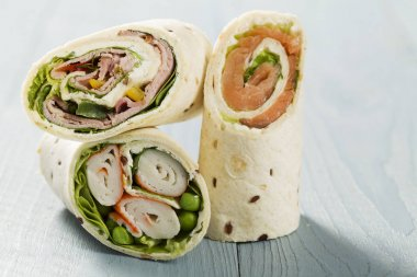 Mix of wraps with ham, chicken, salmon and crab served