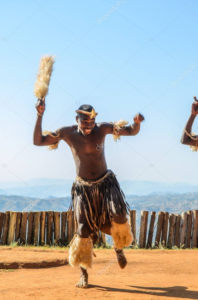 Zulu man dancing dressed in traditional gear. Valley of a