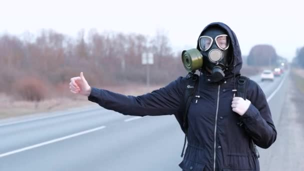A girl in a gas mask stands on the edge of the road and tries to stop the car.