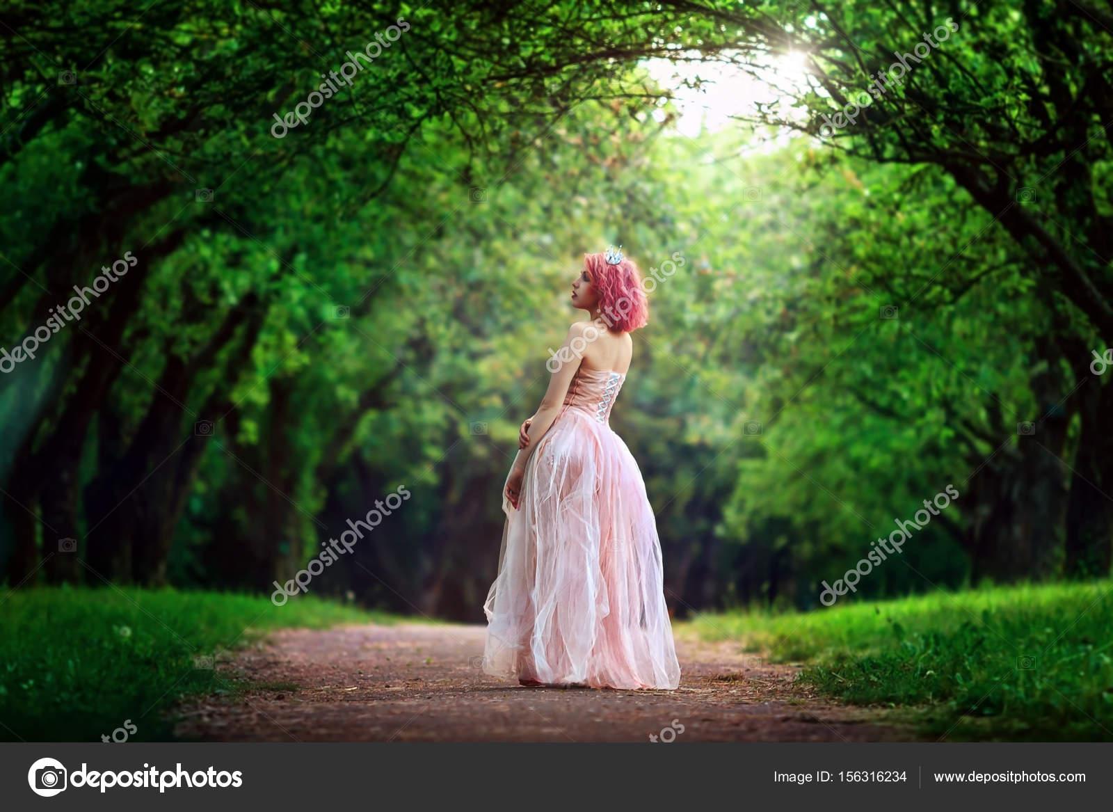 4fa78c732 Retrato de una hermosa muchacha en el vestido rosa. Se encuentra en el  paseo. Retrato de mujer romántica en el bosque de hadas.