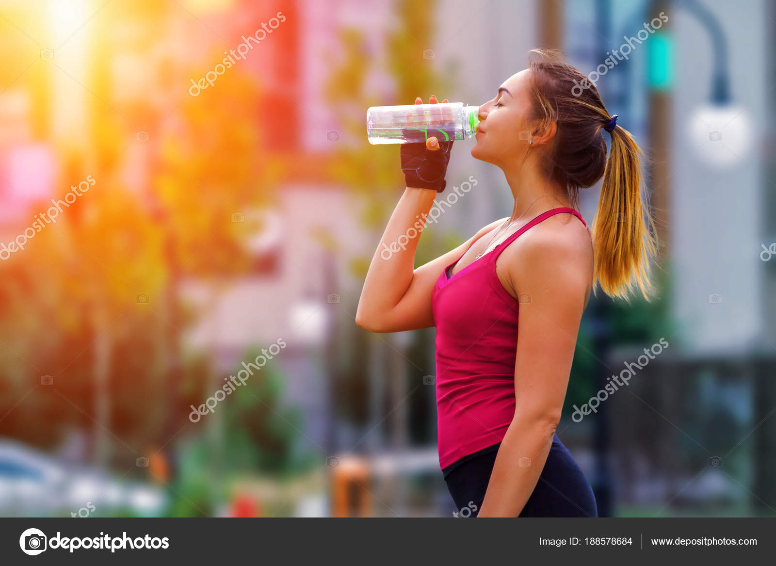 Woman in sport clothes drinking water after workout at city