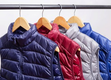 family concept or showroom of down vest jackets hanging on a hanger in the wardrobe
