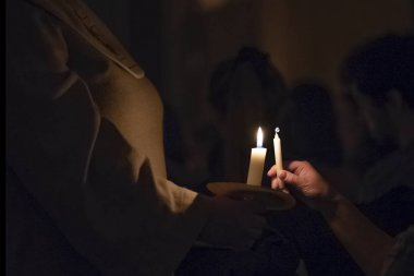 Woman in the traditionall religious habit dress in the church shares candle fire. Celebration of Lucia day in Sweden