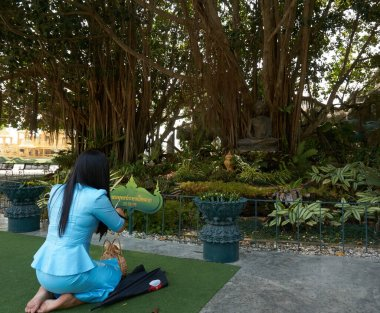 Chiang Rai, Thailand - February.10.2020: Women praying next to buddha statue under bodhi tree in White Temple Rong Khun temple