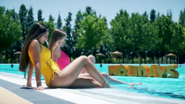 Summer concept. Two girls in the pool and the word Holidays in 3D floating. 3D Render and Real Footage Compositing