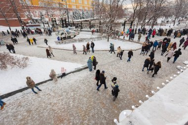 MOSCOW, RUSSIA - JANUARY 4, 2019: Snow-covered Manezhnaya square in Moscow, citizens and tourists walk through the Christmas center of the city, on the street decorated with Christmas trees and entertainment