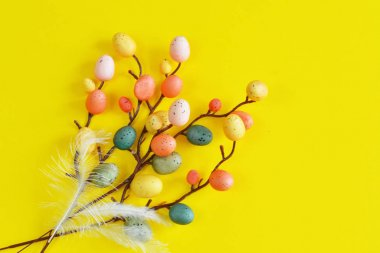 multi-colored quail eggs on a yellow background. Easter Postcard Template