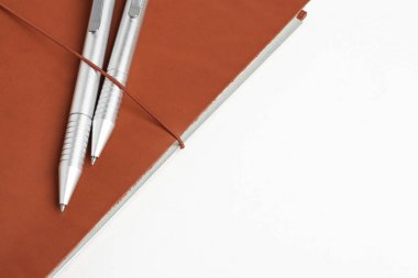 Red Leather Journal Cover With Two Ballpoint Pens