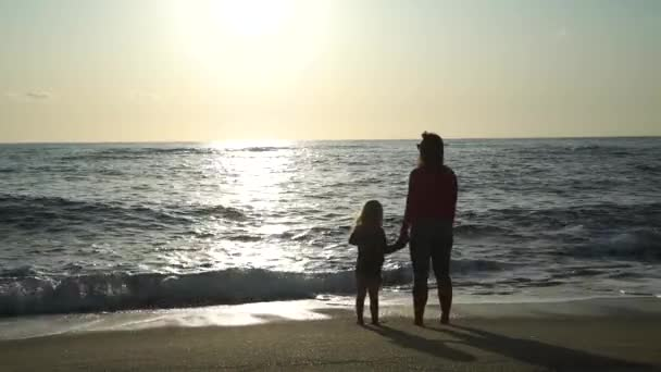 Woman with Daughter Standing on a Beach at Sunset