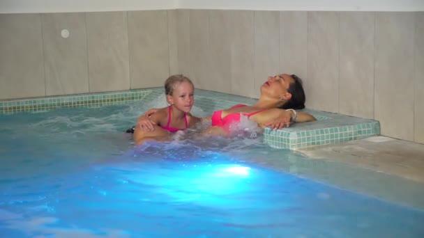 Žena a dcera v bazénu s hydromasáží