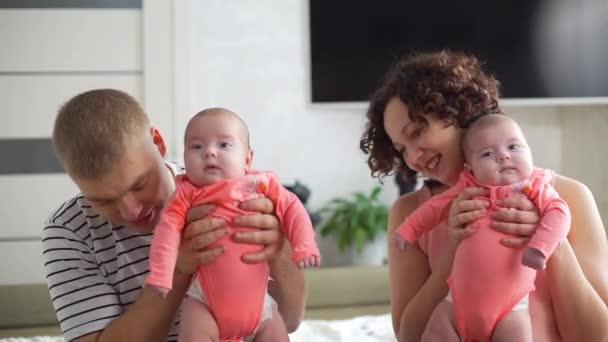 Mladí rodiče v domácím držení Twin děti