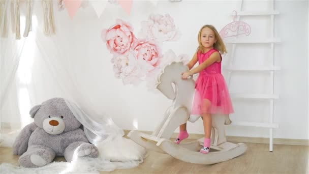 Cute Little Girl Riding a Toy Rocking Horse