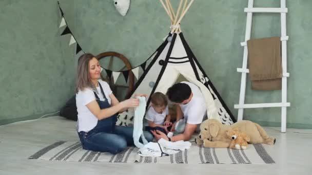 Žena skládací oblečení v blízkosti svého manžela a syna