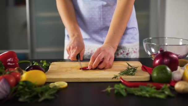 Young Woman Slicing Chili Pepper in the Kitchen