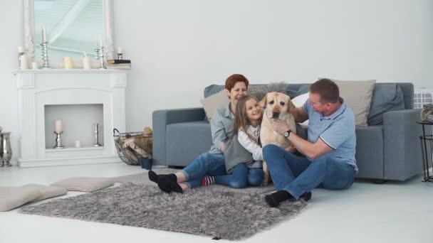 Rodina sedí u pohovky se svým psem