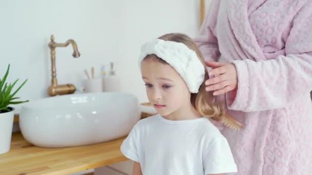 Mladá matka kartáčování její dcery vlasy doma