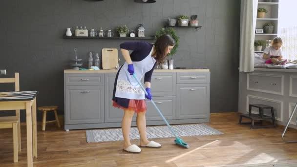 Junge Frau wischt den Boden in der Küche