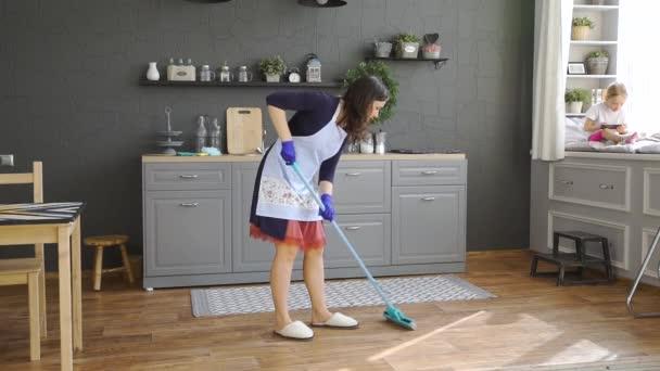 Mladá žena stěr prach pomocí mop doma