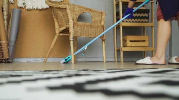 Mladá žena praní podlahy pomocí mokré mop podložky