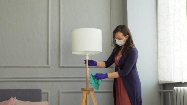Manželka v domácnosti v ochranné masce čistí podlahovou lampu