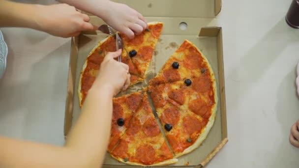 Ruce ženy řezání pizza s nožem