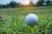 golfový míček na zelené trávě. Golfový míček na odpališti ve večerním golfovém hřišti se slunečním zázemím.