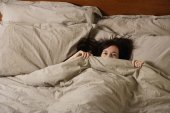 woman peering out from under covers