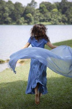 Teen girl running by lake