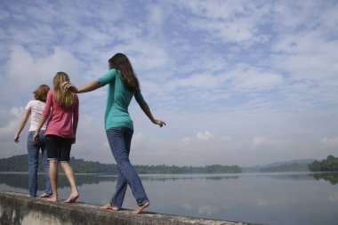 girls walking on wall