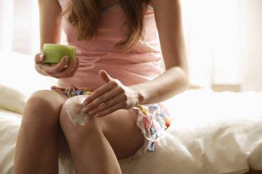 woman applying lotion to knee