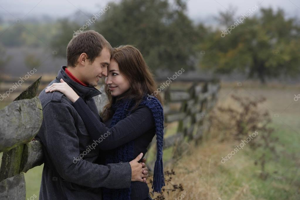 couple embracing against country fence