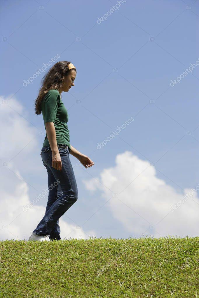 Teen girl walking on grass